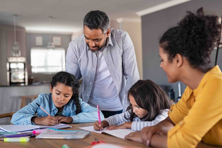 Mixed race parents helping children in homework at home